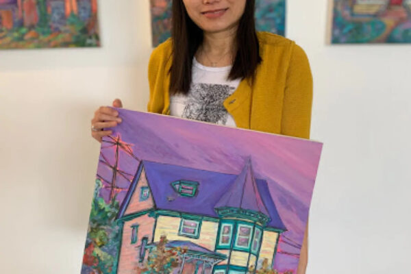 Aeris Osborne holding one of her paintings