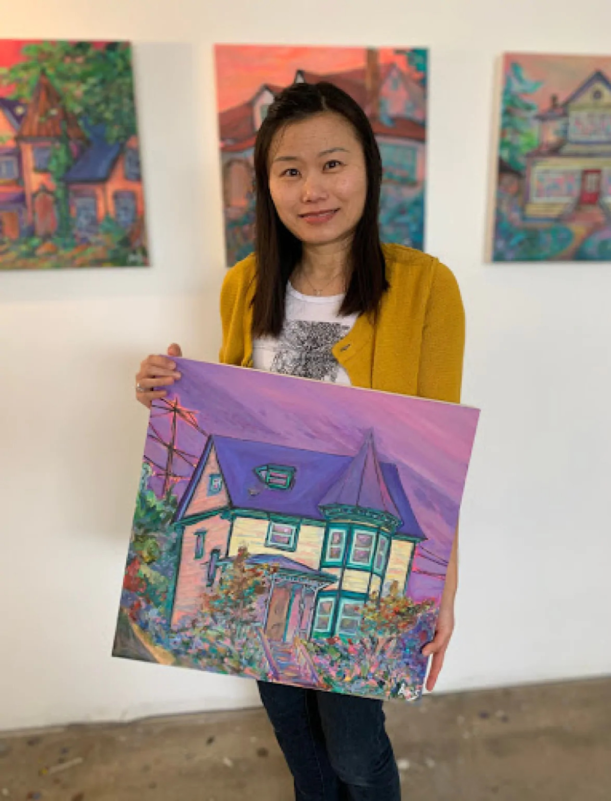 Aeris Osborne holding one of her paintings