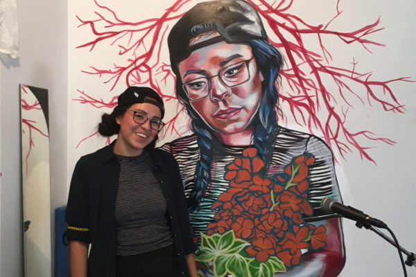 Lauren Crazybull standing with her mural